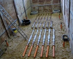 sechs gleiche Rohrleitungsabschnitte liegen in großem Versuchsstand im Sand