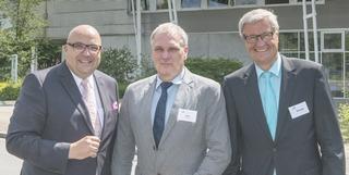 drei Männer in Anzug und Krawatte vor Bürogebäude