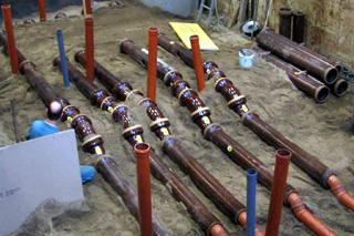 Leitungen aus braunen Abwasserrohren aus Steinzeug und Kunststoff bilden Teststrecken für Prüfungen