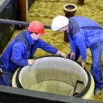 Männer in Arbeitskleidung montieren einen Abwasserschacht