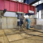 Mann mit Helm in Arbeitskleidung arbeitet an blauem Hydraulikzylinder, der an rotem Stahlträger hängt
