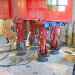 vier rote Hydraulikzylinder hängen unter rotem Stahlträger