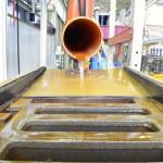 in Prüfanlage läuft Flüssigkeit aus orangefarbenem Abwasserrohr in Straßeneinlauf