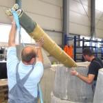 zwei Männer führen an einer Testanlage einen Packer mit Kurzliner in einen Abwasserschacht ein