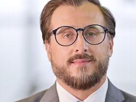 Portrait von Mann mit dunkler Brille und dunklen Haaren