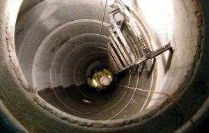 Blick von oben in Abwasserschacht mit Person in Arbeitskleidung mit Helm auf Schachtboden