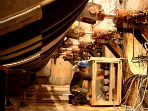 Person mit blauem Helm an Schaltkasten unter Druckzylindern von Rohrvortriebssimulator