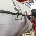 Mann mit Brille und orangefarbener Jacke untersucht Riss in Kanalrohr