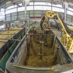 gelber Saugbagger entnimmt Sand aus mittelformatigem Versuchsstand, mit Fischaugenobjektiv aufgenommen