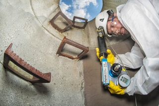 Mann mit weißer Schutzbekleidung und gelben Hanschuhen im Abwasserschacht hält blaues Prüfgerät