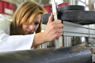 Wissenschaftlerin stellt Prüfgerät für Prüfung an schwarzem Fernwärmerohr ein