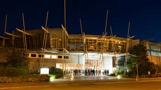 Personen vor IKT-Institutsgebäude bei Nacht