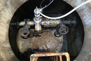 Blick in Schacht mit Abwasserdruckleitung und Armaturen