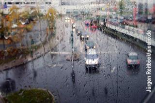 Blick durch nasses Fenster auf Straße und Platz
