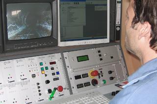 Mann sitzt vor Schaltpult und Monitoren