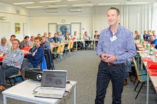 Blick in Veranstaltungsraum mit Teilnehmern und Referent