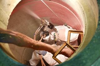 Blick von oben in Schacht, Sanierer mit Spritzpistole beschichtet Schachtwand