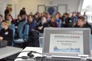 Laptop-Monitor mit PowerPoint-Folie im Vordergrund, Teilnehmer im Hintergrund