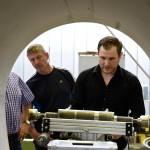 Blick durch großes Rohr auf MAC-Gerät, IKT-Wissenschaftler und Teilnehmer