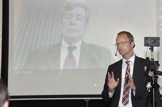 Mann mit Anzug vor Leinwand führt Webkonferenz