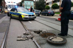 Tagesbruch in der Straße neben Schienen und Schacht, Polizeiabsperrung