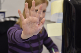 Frau in gestreiftem Pullover streckt die Hand in Richtung Kamera aus