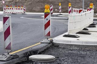 Baustelle Straße mit Baken und Abspergittern und Kanaldeckel