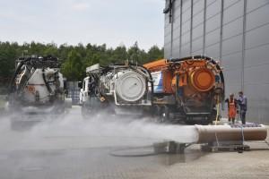 Wasser spritzt aus Rohr vor drei Kanalreinigungsfahrzeugen