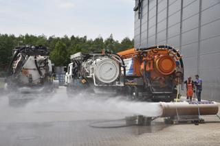 Wasser sprüht aus Rohr vor drei Kanalreinigungsfahrzeugen