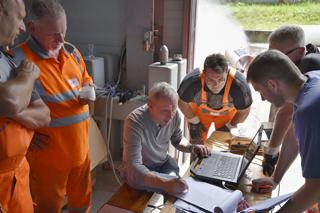 Mann sitzt vor Laptop, Personen in Arbeitskleidung stehen um ihn herum