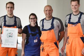 Gruppenbild mit vier Personen in Arbeitskleidung, ein Mann hält eine Urkunde