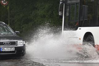 Auto und Bus auf überfluteter Straße