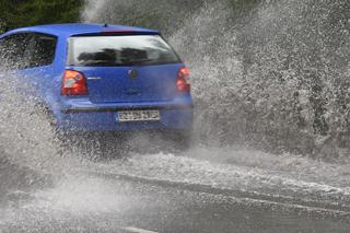 blaues Auto fährt über überflutete Straße