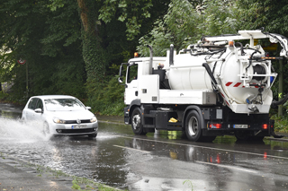 Spülfahrzeug bei überfluteter Straße