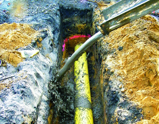 gelbes Rohr in einem offenen Leitungsgraben