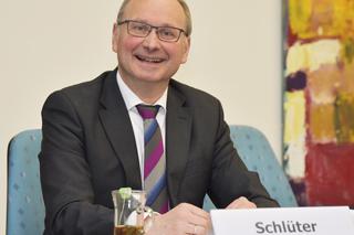 Mann mit Brille, Anzug und gestreifter Krawatte lacht