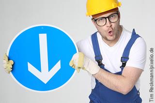 Bauarbeiter mit blauer Hose und gelbem Helm hält blau-weißes Schild mit Pfeil