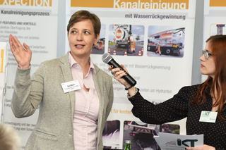 Interview mit Frau in hellem Blazer an Messestand