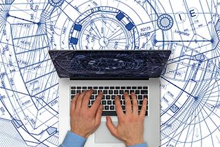 Mann mit Laptop über Bauplänen