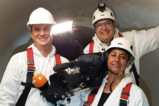 Reporter, IKT-Geschäftsführer und Kamerafrau mit Schutzausrüstung in Kanalrohr