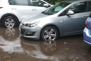 mehrere Autos stehen in tiefer Pfütze während es regnet