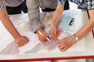 drei Männer über eine Stadtkarte gebeugt