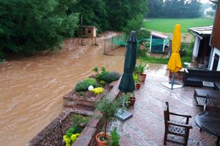 Bach mit Hochwasser überflutet Grundstück