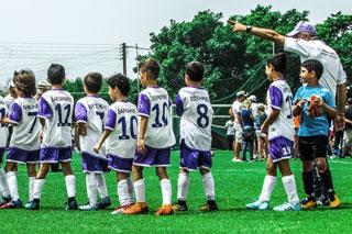 Fussballtrainer gibt Kindermannschaft Anweisungen