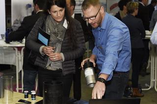 Mann mit Brille und blauem Hemd zeigt Frau mit Mappe unter dem Arm technische Produkte