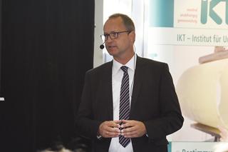 Mann in Anzug vor Leinwand während seines Vortrags