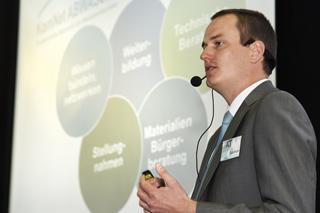 Mann in Anzug vor Leinwand hält einen Vortrag