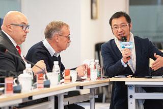 drei Personen bei Konferenz, Roland Waniek links, Min Liu rechts mit Mikrofon