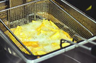 goldgelbe Pommes Frites in Fritteuse mit heißem Öl