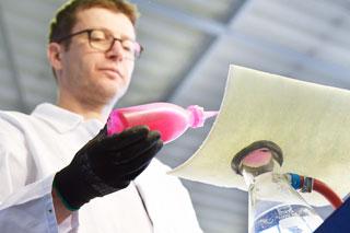 Mann mit weißem Kittel in Labor hält Flasche mit pinker Flüssigkeit über Schlauliner-Probe
